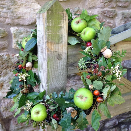 An Autumn wreath full of hedgerow finds, seasonal foliage, seedheads and orchard fruits.